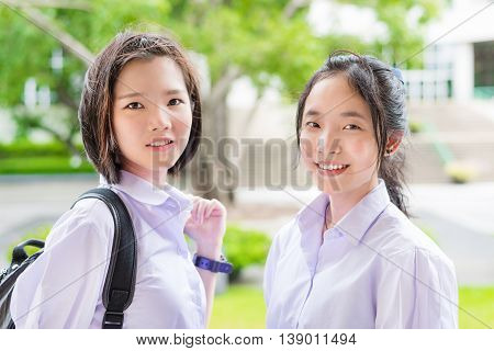 Cute Asian Thai high schoolgirls student couple in school uniform standing with her friend in a happy smile face expression