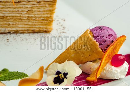 Ice cream in waffle cone and cake served with red berry sauce decorated with flower on white background