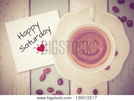 Happy Saturday on paper note with coffee cup on table