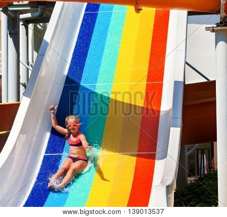 Child little girl on water slide at aquapark hand up . There are some water slides with flowing water in aqua park. Summer water park holiday. Happy summer. Outdoor.