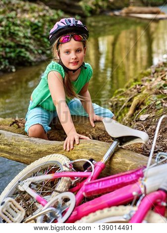 Bikes cycling child girl. Girl rides bicycle. Girl cycling fording throught water on log. Cycling trip is good for health. Cyclist watch at camera.