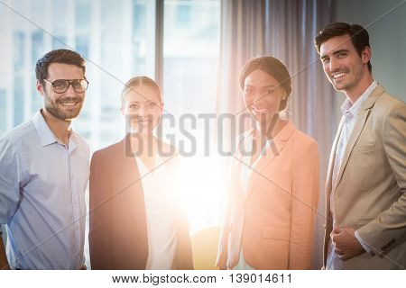 Businessmen and businesswomen posing together in the office