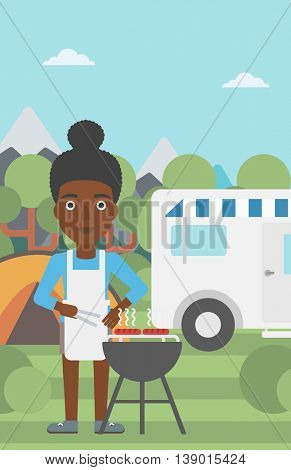 An african-american woman cooking meat on barbecue on the background of camper van. Woman travelling by camper van and having barbecue party. Vector flat design illustration. Vertical layout.