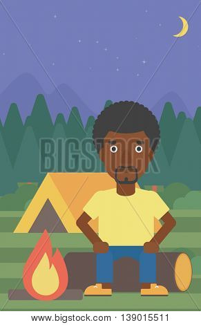 An african-american travelling man sitting on a log near a fire on a background of camping site with tent. Man sitting near a campfire at a campsite. Vector flat design illustration. Vertical layout.