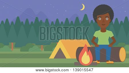 An african-american woman sitting on a log near a fire on a background of camping site with tent. Woman sitting near a campfire at a campsite. Vector flat design illustration. Horizontal layout.