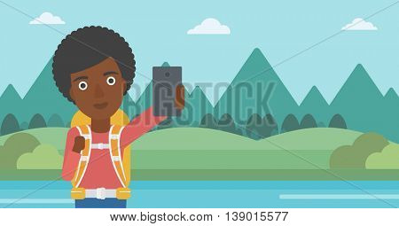 An african-american woman making selfie on the background of mountains. Travelling woman with backpack taking photo with cellphone. Vector flat design illustration. Horizontal layout.