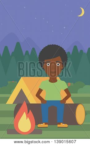 An african-american woman sitting on a log near a fire on a background of camping site with tent. Woman sitting near a campfire at a campsite. Vector flat design illustration. Vertical layout.