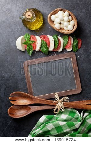 Caprese salad. Mozzarella cheese, tomatoes and basil herb leaves over stone table. Blackboard for your text. Top view with copy space