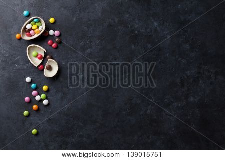 Colorful candies and chocolate egg on stone background. Top view with copy space