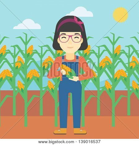 An asian female farmer holding a corn cob. Young farmer standing on the background of corn field. Vector flat design illustration. Square layout.