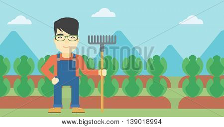 An asian friendly farmer holding a rake. Farmer standing on the background of cabbage field. Vector flat design illustration. Horizontal layout.
