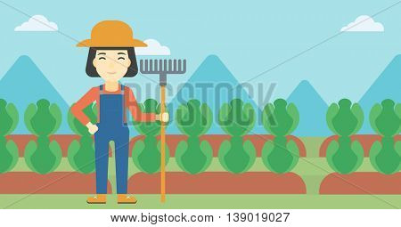 An asian female farmer holding a rake. Friendly farmer standing on the background of cabbage field. Vector flat design illustration. Horizontal layout.