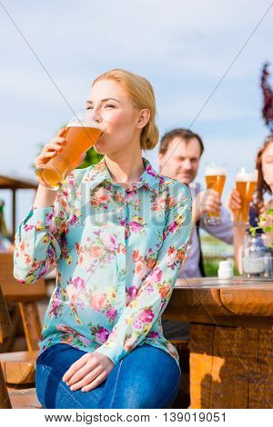 Woman drinking with friends in beer garden