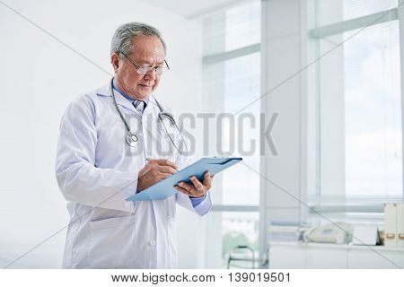 Portrait of experienced Vietnamese doctor making notes
