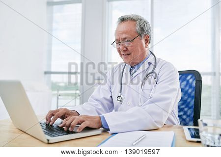 General practitioner working on laptop at his table