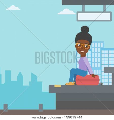 African-american young woman sitting on a suitcase at the train station on the background of arriving train. Woman waiting for a train at the platform. Vector flat design illustration. Square layout.