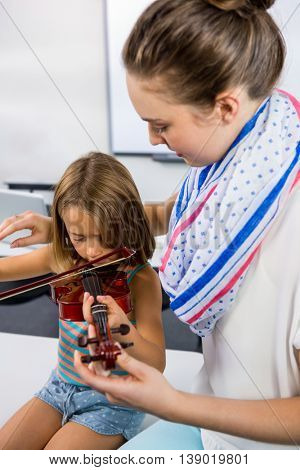 Close-up of teacher assisting girl to play violin whiteboard in classroom