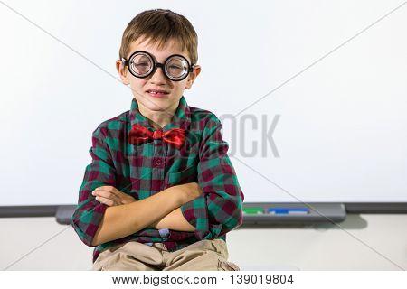 Portrait of boy sitting against whiteboard in classroom