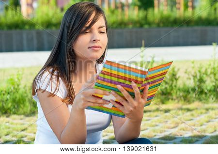 Female Sitting And Reading From Journal Or Agenda