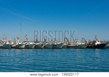 Boats yachts on turquoise blue water with sun specks reflections on boards against clear blue sky on the background. Summer vacation scene with copy space