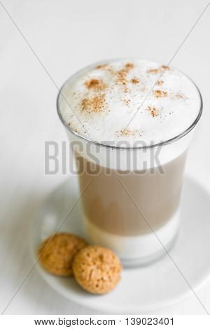 Glass of delicious cafe latte with biscotti on white plate and table