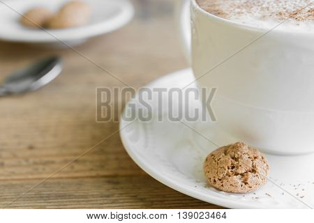 Cup of latte coffee with biscotti arranged on old rustic wooden table