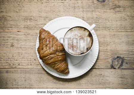 Cup of latte macchiato coffee with croissant on white plate arranged on old rustic wooden table. Top view