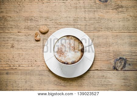 Cup of cappuccino coffee with biscotti on wooden table. Top view