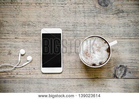 Cup of latte coffee with white modern smartphone and earphones on old rustic wooden table. Top view