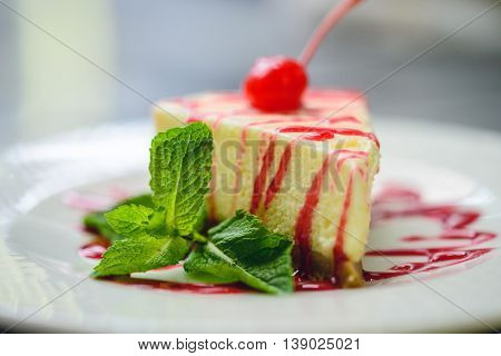 Cherry tasty cheesecake decorated by mint prepared at cafe