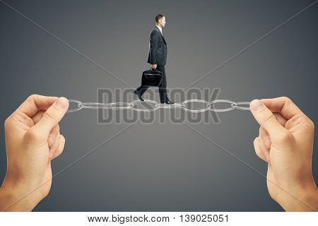 Balancing concept with businessman miniature walking on chain held by hands on dark background