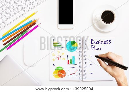 Hand writing business plan in spiral notepad placed on white office desktop with various objects