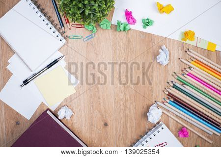 Top view of messy wooden table with colorful pencils notepads crumpled paper balls decorative plant and other items. Mock up