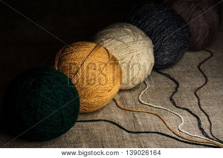 Multi-colored woolen clews for knitting on a burlap background