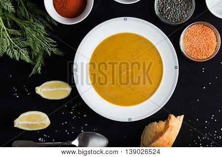 Cream Soup Of Assorted Lentil. Yellow And Green Lens, Spices As Raw For Meal And Lemon On Black Back
