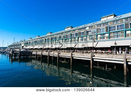 Finger wharf restaurants and hotel in Woolloomooloo bay with unrecognisable people in the distance. Sydney Australia