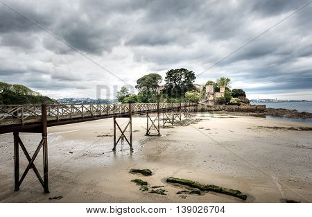 Landscape photo of old bridge in Santa Cruz island Oleiros Rias Altas A Coruna Spain in low tide.