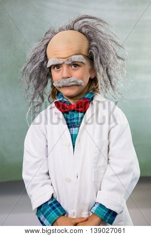 Portrait of boy dressed as scientist standing against board in classroom
