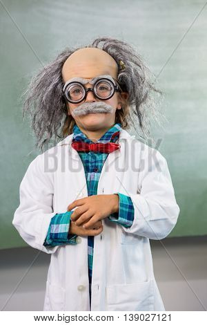 Portrait of boy dressed as scientist posing agains board in classroom