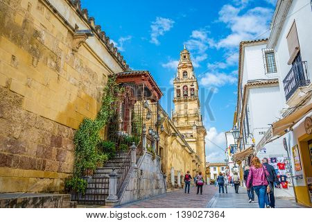 Cordoba, Spain - May 20, 2016: Traditional architecture of cordoba and tourists walking on the street in a day time