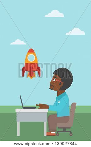 An african-american businessman sitting at the table and looking at a flying rocket. Businessman working on a laptop. Business start up concept. Vector flat design illustration. Vertical layout.
