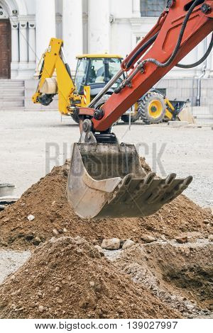 Excavator dipper at construction site in a city square