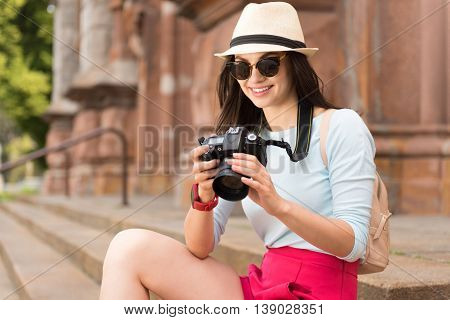 Amateur photographer. Positive delighted smiling woman sitting on the footsteps and resting while holding photo camera