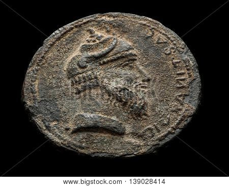 Ancient coin with head isolated on black angle shot