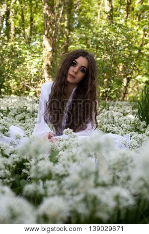 Beautiful woman in long white sitting in a forest surrounded by a sea of white flowers