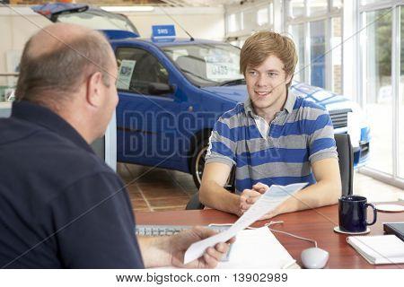 junger Mann schreibarbeit in Autosalon ausfüllen