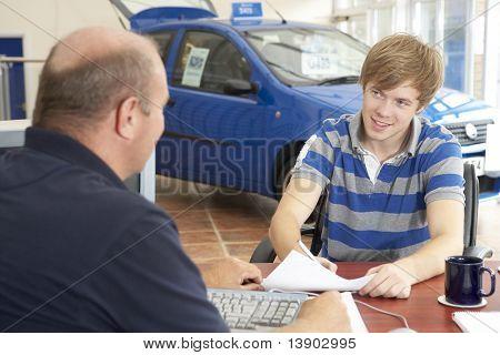 junger Mann ausfüllen Papierkram im Autohaus