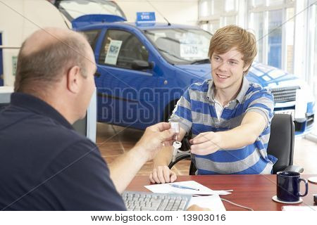 Young man filling in paperwork in car showroom