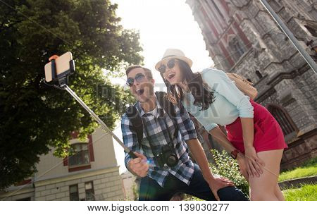 Brighten your life. Cheerful content smiling couple using selfie stick and making photos while having a walk