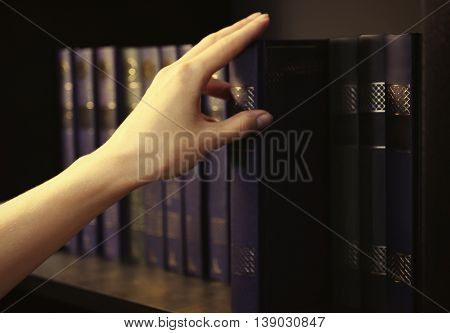 Books in a row on a bookshelf. Hand taking a book